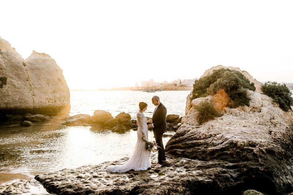 Dieses Bild zeigt das Brautpaar bei einer Hochzeit am Stand von Ferragudo in Portugal, an der Algarve. Die Braut trägt ein Brautkleid von Jolie Brautmoden, Bruchsal bei ihrem Elopement und Freier Trauung mit Blick auf das Meer.