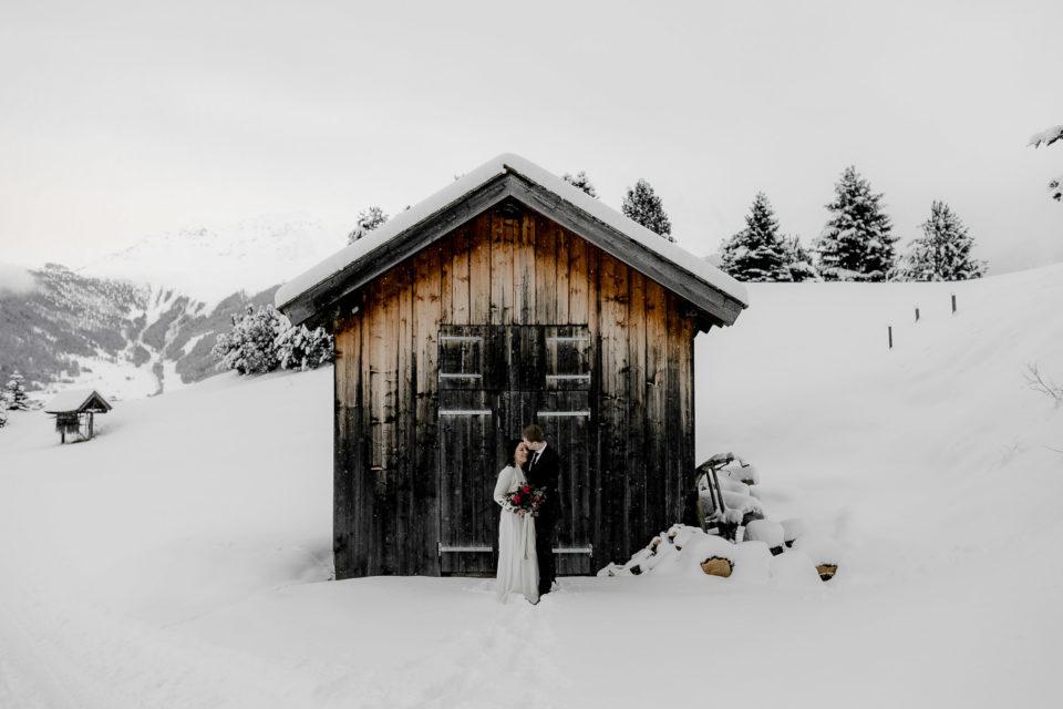 Das Brautpaar bei ihrer Hochzeit in den Bergen, in Serfaus, Tirol, im Schnee. Die Braut trägt ein Brautkleid von Elfenkleid und hält ihren wilden Winter boho Brautstrauß, mit roten Rosen, Beeren, Eukalyptus und einem Seidenband.