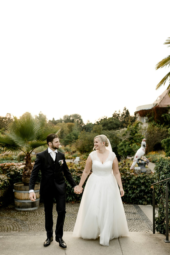 Dieses Bild zeigt das Brautpaar bei einer Hochzeit im Botanischen Garten in München. Die Braut trägt ein weißes Brautkleid mit Spitze im Oberteil und einen weißen Schleier.