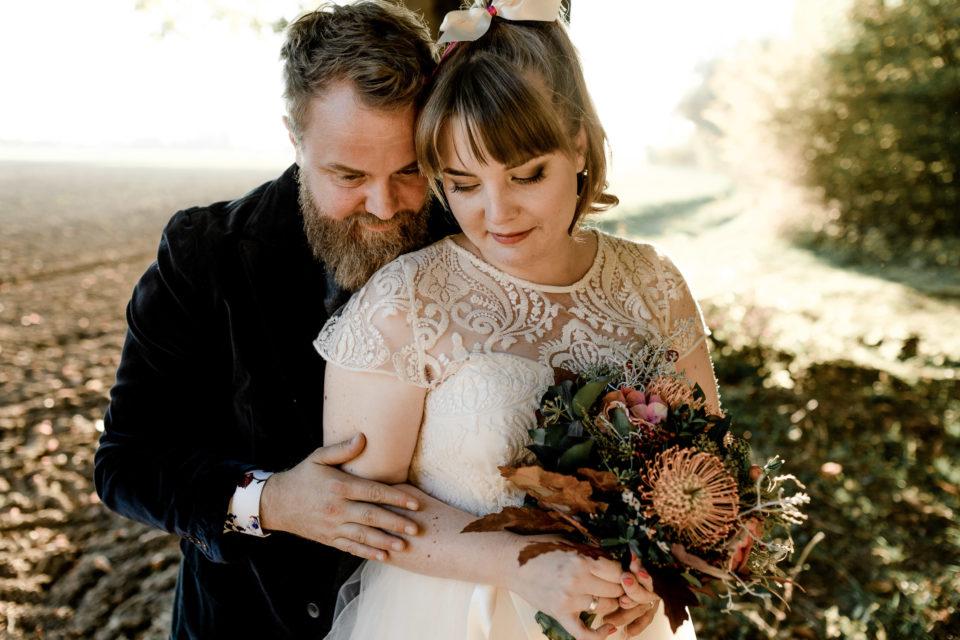Brautpaar mit dem Hochzeitsmotto Alice im Wunderland, bei ihrer Herbsthochzeit in München. Die Braut hält ihren wilden boho Herbst Brautstrrauß in den Farben orange rot.